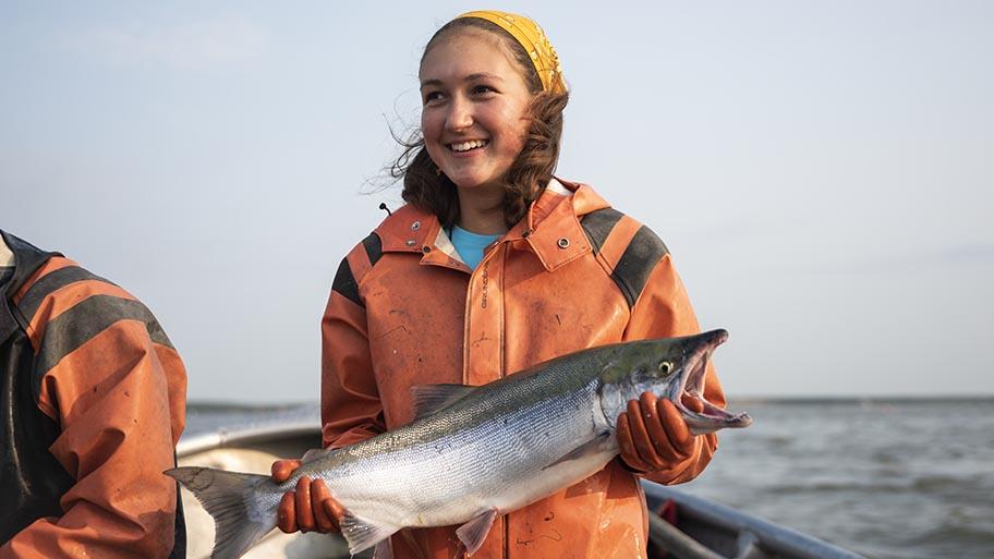Fischerin hält Lachs in der Hand