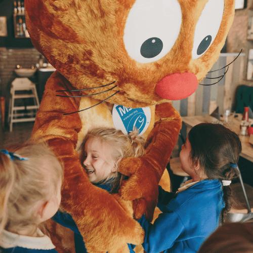 Enfants dans les bras de la mascotte