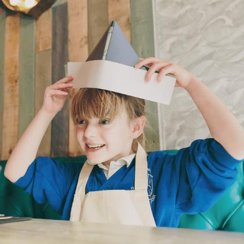 Enfant avec un bateau en papier