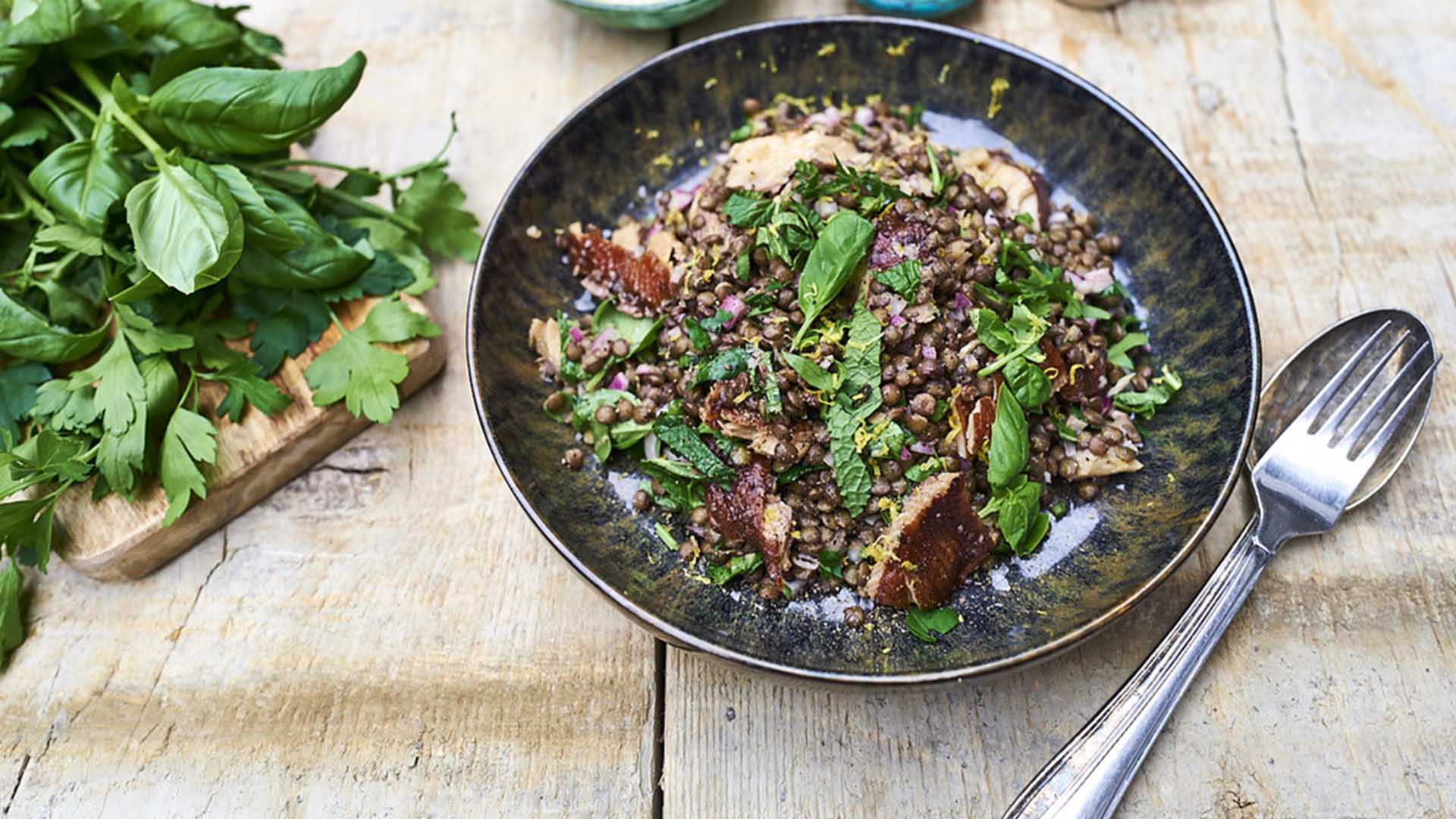Lentils, herring and leaves in dark bowl on wooden table with fork and spoon on side