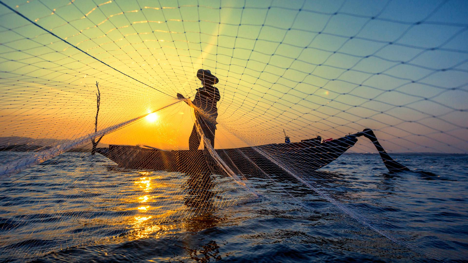 Fisherman throwing a net with the sunset behind him