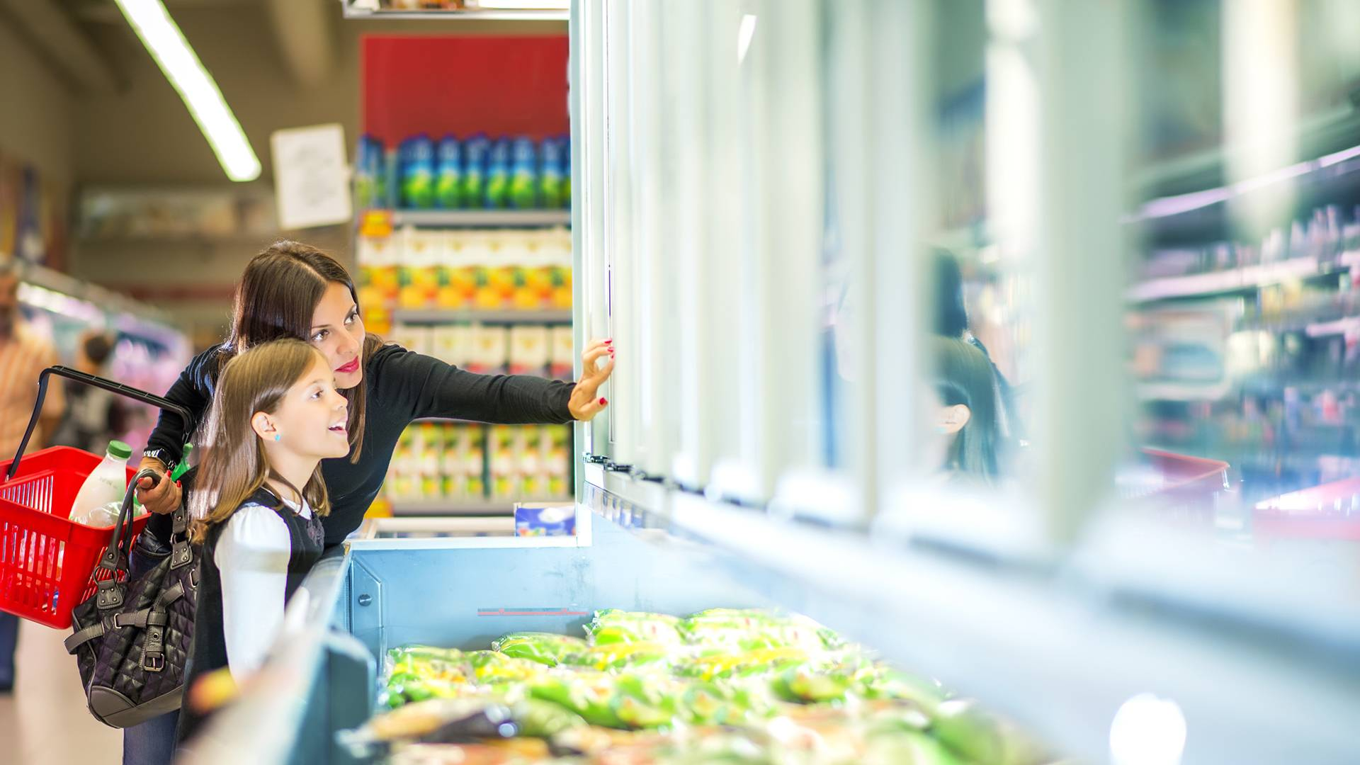 Woman and daughter choosing frozen food in supermarket