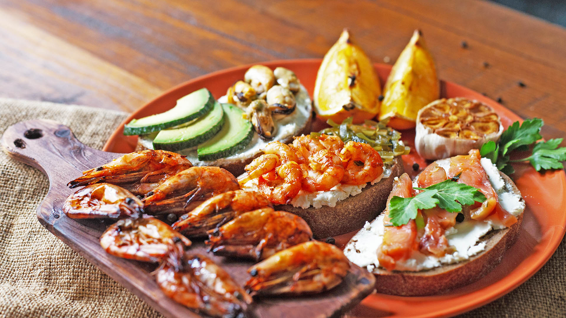 """Seacuterie"" board with prawns, shellfish, salmon and avocado on slices of bread"