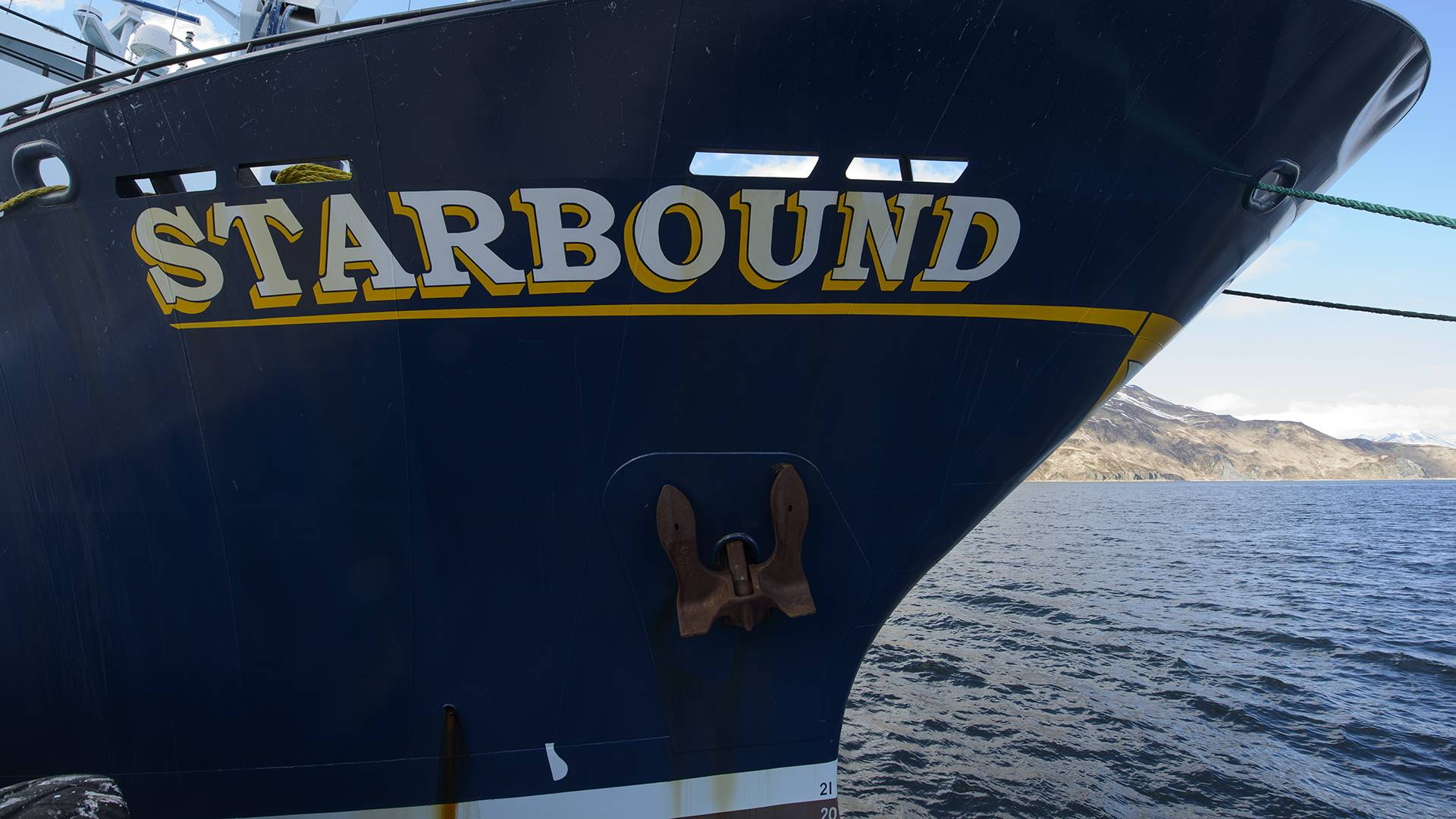 """A shot of the front of a large blue boat on the water with """"Starbound"""" painted on the front."""
