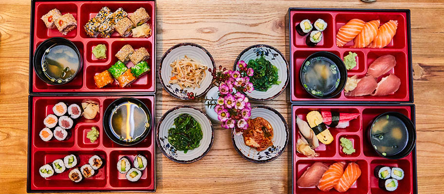 Two Japanese bento boxes from above with sashimi, nigiri, miso soup and plates of tsukemono pickles between