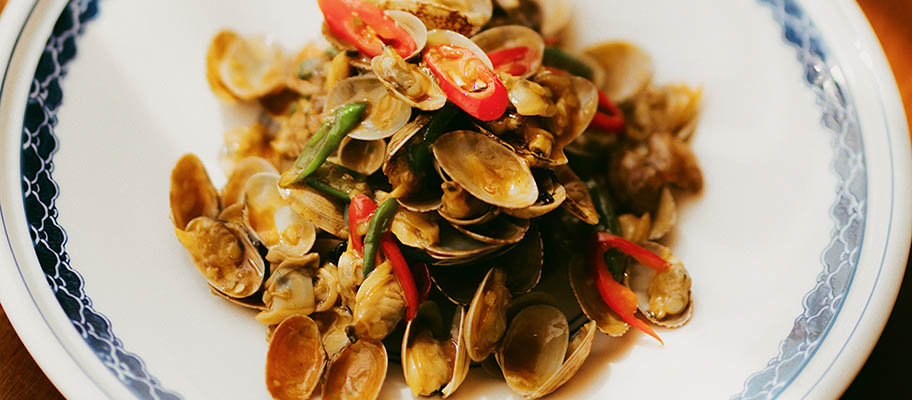 Bowl of clams with sliced chilis from above.