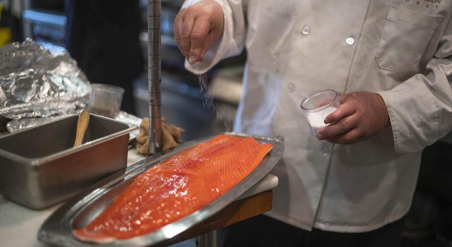 White coated chef sprinkling salt on salmon fillet