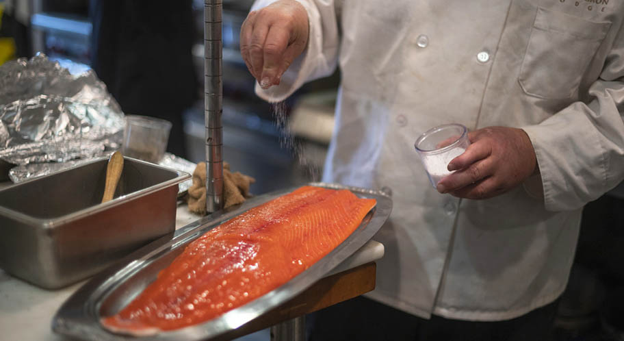 White coated chef sprinkling salt on salmon fillet