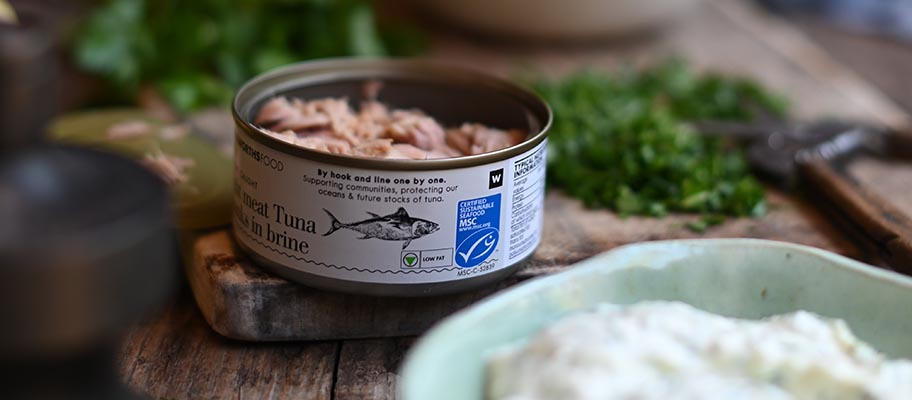 Can of tuna with MSC label on board with bowl of mayonnaise