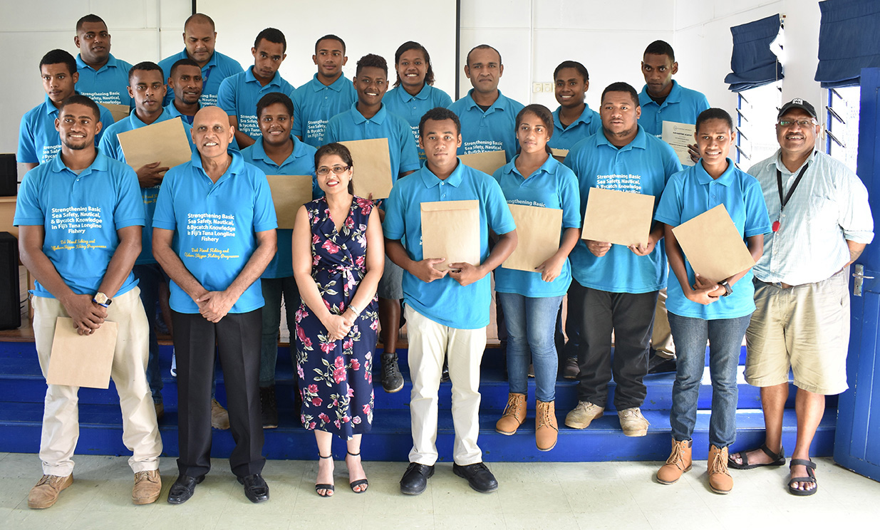 A group of students from Fiji National University in blue shirts standing in two rows holding certificates