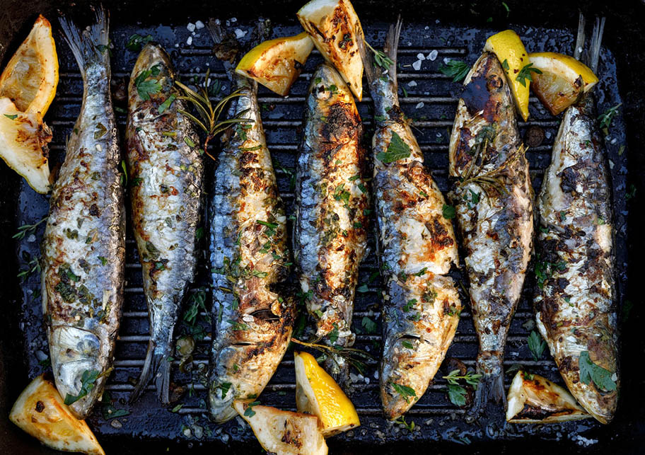 Grilled sardines with lemon pieces on a grill plate.