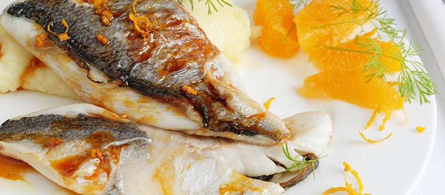 Hake fish fillets on white plate with saffron and pieces of mandarin orange