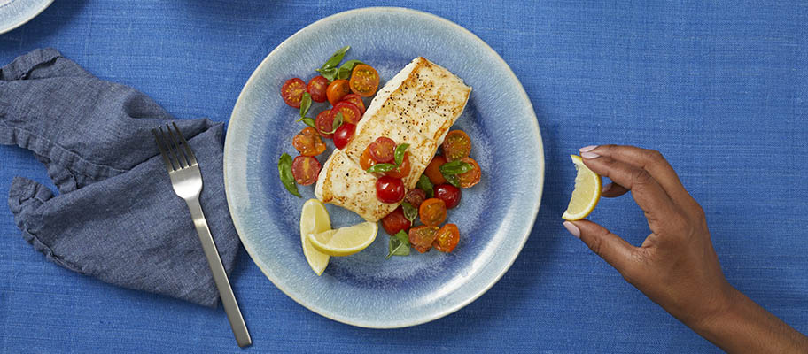 Plate of halibut with tomatoes and lemon slices on blue tablecloth with hand squeezing lemon