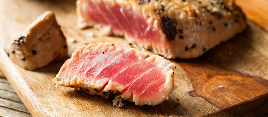Grilled tuna steak on wooden chopping board