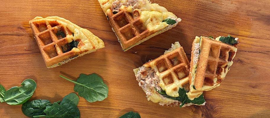 Four quarters of waffle with tuna and cheese on wooden surface with leaves