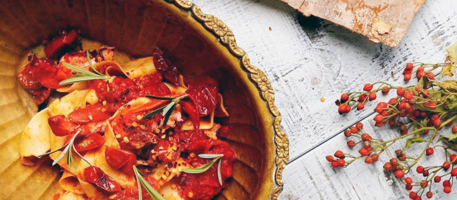 Lobster meat with pasta in wooden bowl with cutlery on wooden board