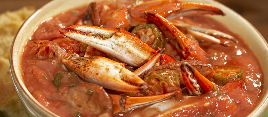 Bowl containing crab claws and sauce