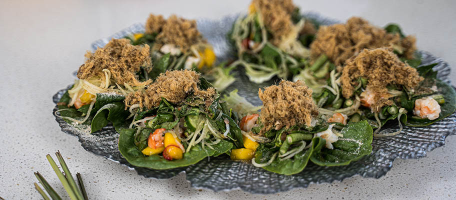 Prawns with leaves and mango pieces on dish