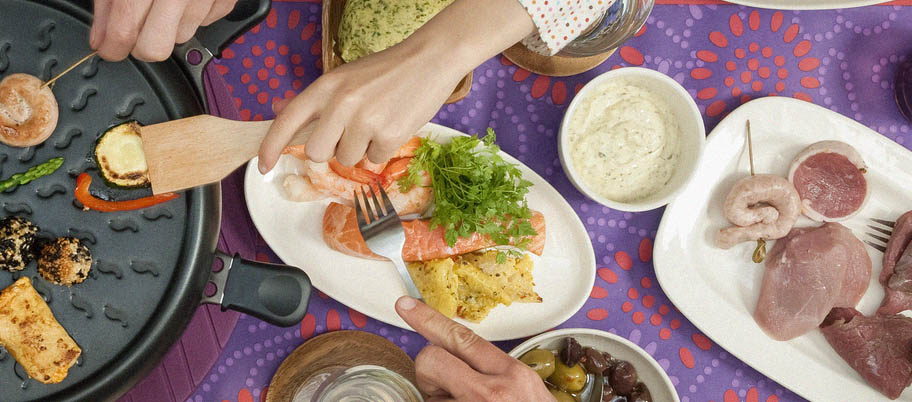 Raclette grill from above with hands reaching for salmon and prawns on side dish
