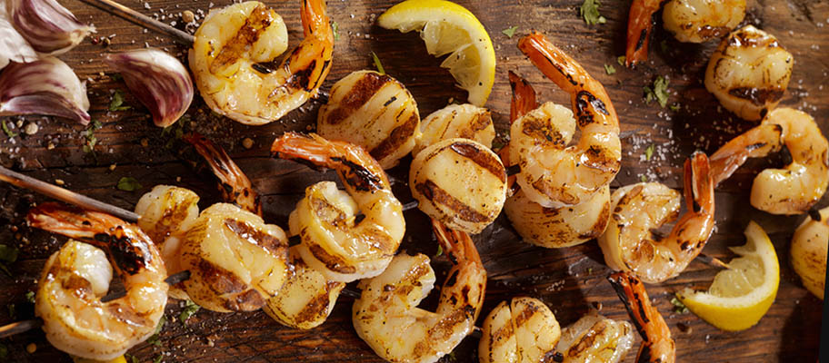 Grilled scallops and shrimp on wooden board with wooden skewers, chunks of lemon and garlic cloves