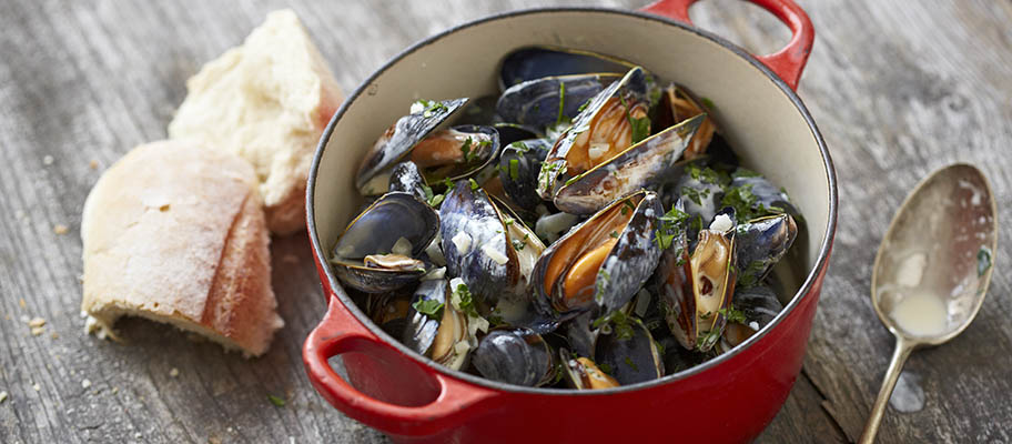 Steamed mussels in red pan with spoon and bread on wooden surface
