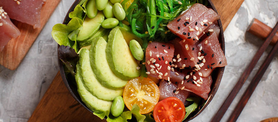 Raw tuna in bowl with avocado, tomatoes and beans, from above