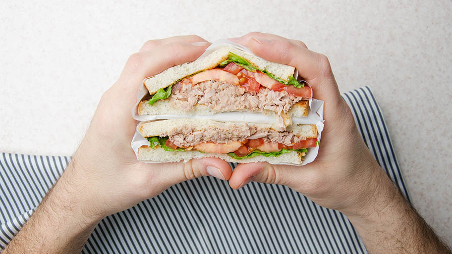 Hands holding tuna sandwich with tomatoes and lettuce