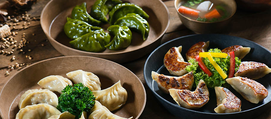 Three bowls with different types of Chinese dumplings on table