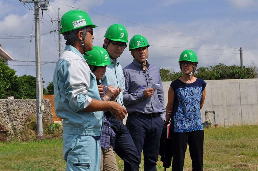 Five people outdoors in green hard hats - Euglena farm assessment