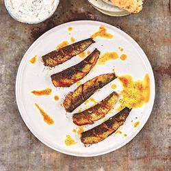 Aerial view of grilled sardines on a white plate with splashes of sauce