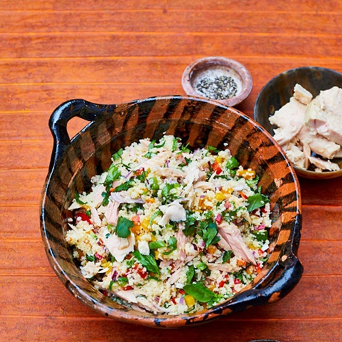 Serving suggestion for couscous tuna salad: in a small bowl with herbs sprinkled on top