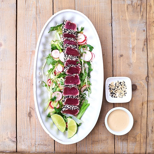 Serving suggestion for tuna tataki - tuna slices positioned in a line down the centre of a long plate