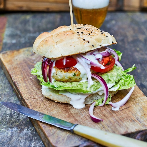 Serving suggestion for tuna burger with guacamole - burger served on a wooden chopping board, with a skewer holding the burger together