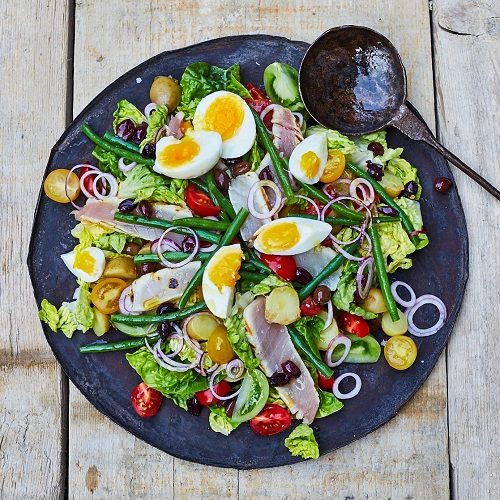 Serving suggestion for  Salade Niçoise: on a large plate with ingredients spread across the whole plate