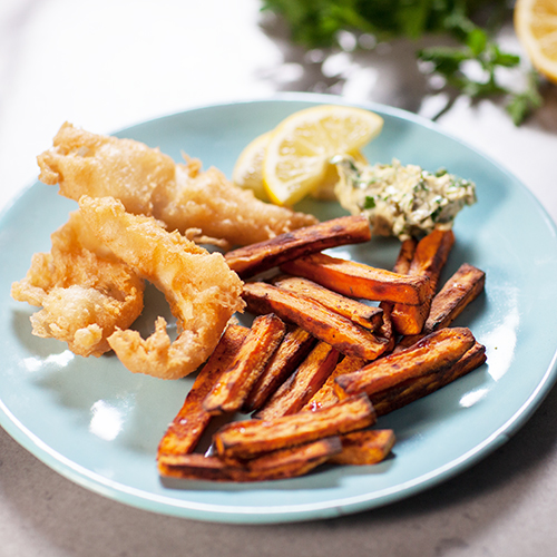 Plated beer battered fish pieces, with sweet potato chips, remoulade and lemon slices