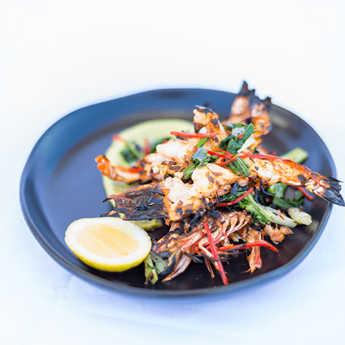 Wild chargrilled Skull Island Tiger Prawns with chilli and garlic oil, avocado mousse and charred greens