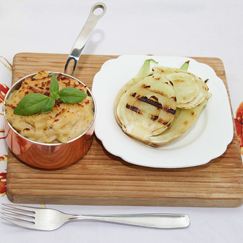 Garnished crab mac and cheese in a small saucepan, with a side of griddled fennel, served on a chopping board.