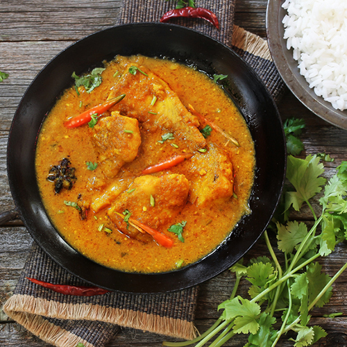 Bowl of Goan fish curry with fresh coriander (front-right), rice (back-right) and dried chillies in the background