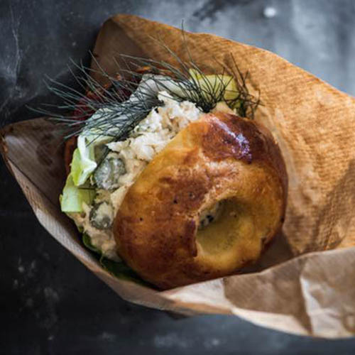 Bagel filled with fish and garnish in paper bag