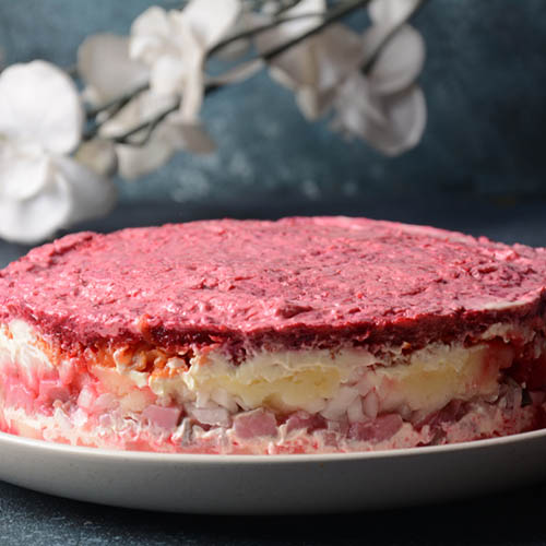 Traditional Russian herring salad close-up with layers of egg and beetroot