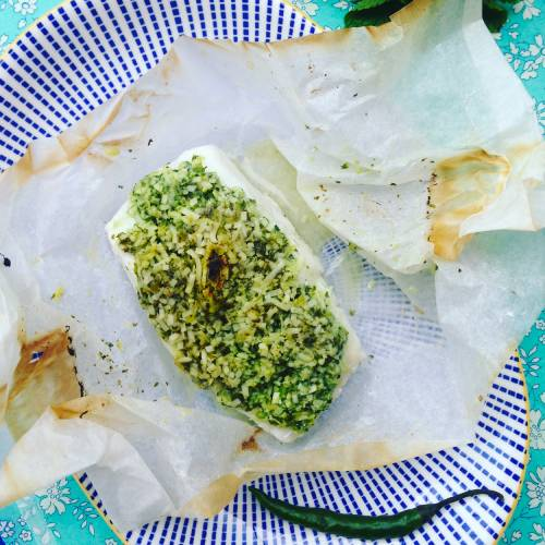 MSC cod filet with herb crust of mint coriander and coconut on a blue striped plate