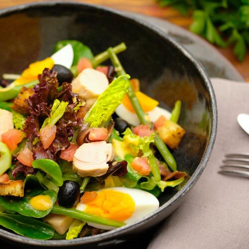 Salat Nicoise in schwarzer Schüssel mit Thunfisch, Bohnen und Ei
