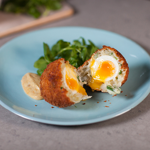 Plated scotch eggs with smoked haddock, served with curry mayo and greens
