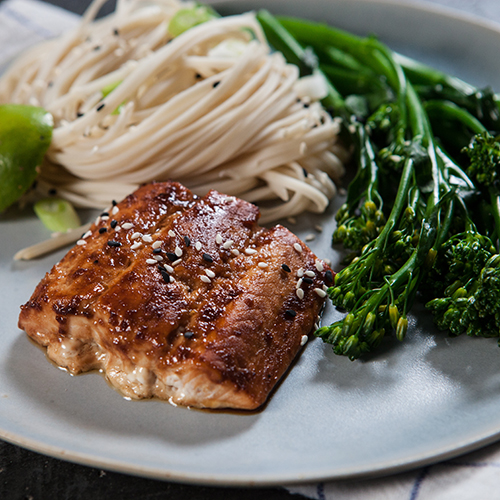 Plated spicy salmon with glaze, served with egg noodles, tenderstem broccoli and lime