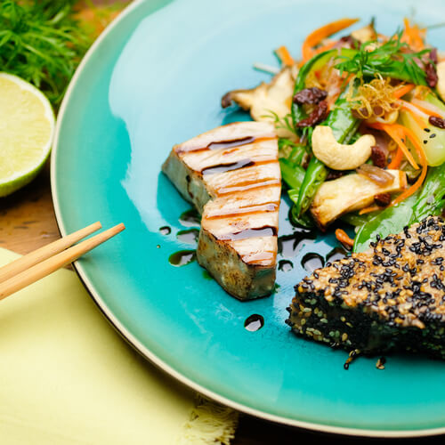 Thunfisch Steak mit Sesamkruste und Cashews auf blauem Teller