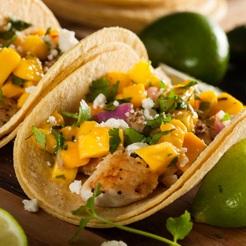 White fish tacos, garnished with mango salsa and coriander