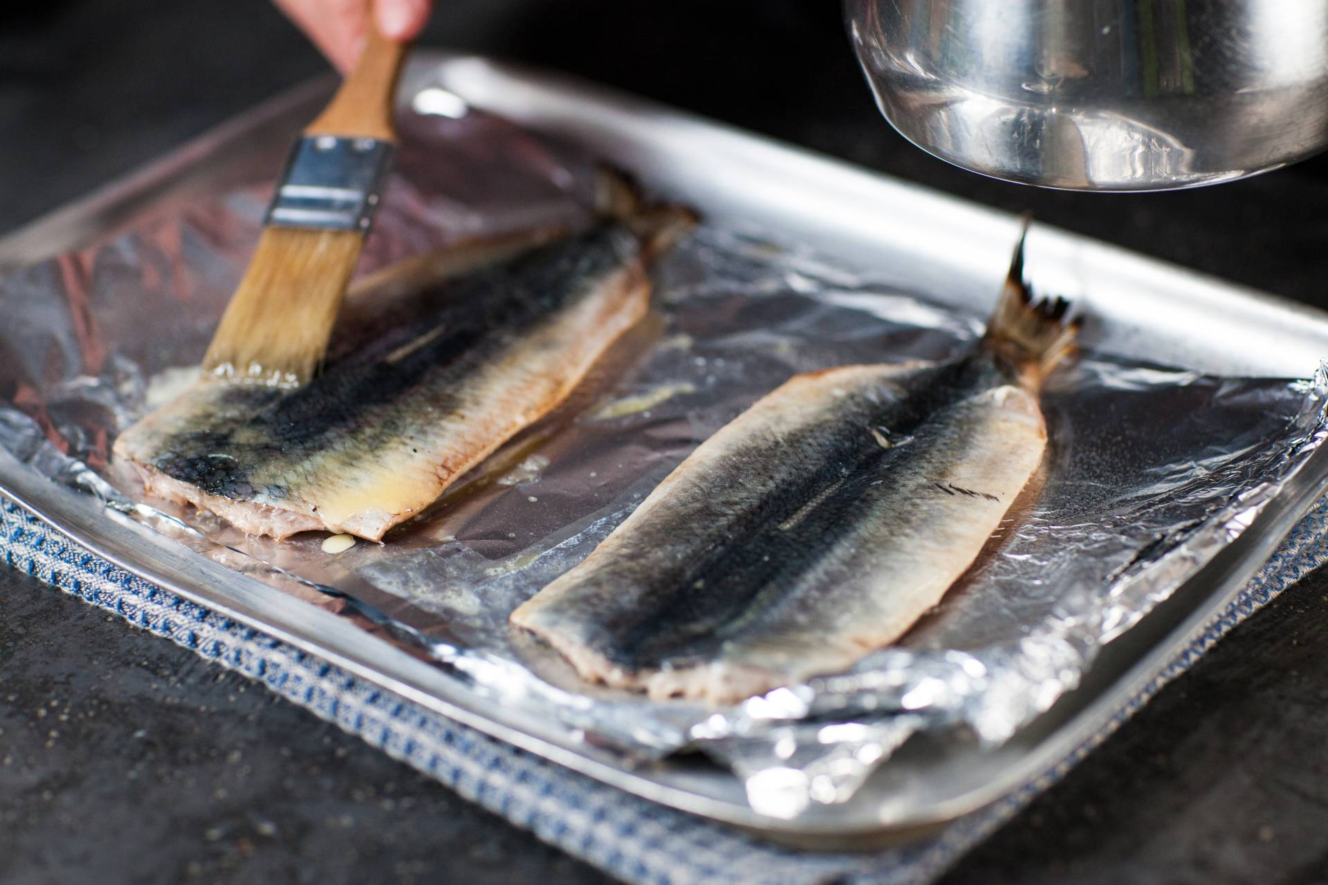 Oil being brushed on herring on a tray