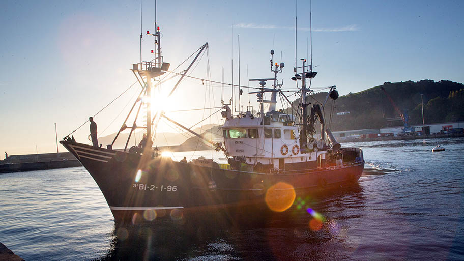 Fishing vessel in harbour against sunset with figure in silhouette on bow