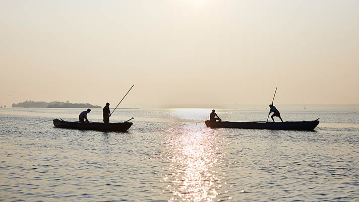 Two small boats with two fishers each, in silhouette against low sun on water