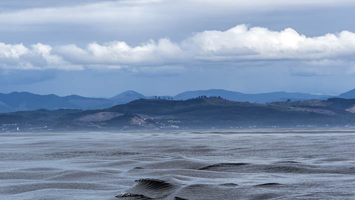 Clouds, mountains and sea with small waves, from West Coast Groundfish Fishery, Newport, Oregon, USA.